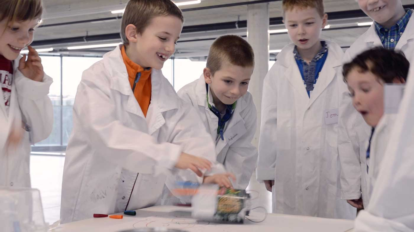 Kids in a laboratory having fun with a scribbling robot they built for a Addictlab Academy birthday party lab