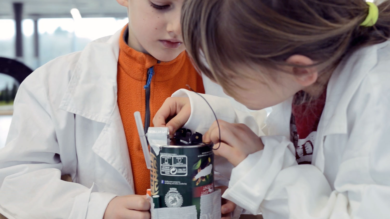 Two kids in a laboratory building a scribbling robot with an empty can.
