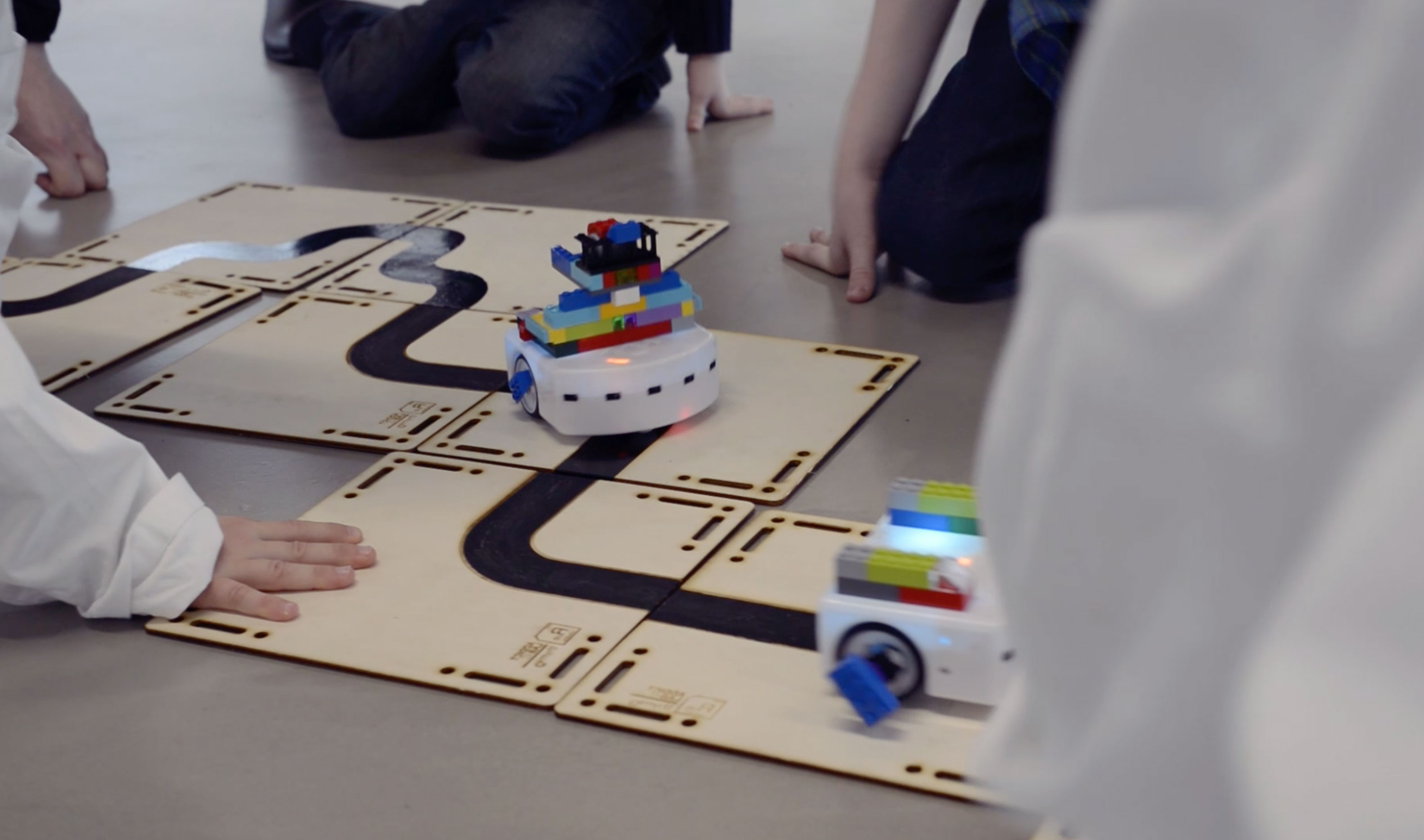 Kids playing with Epfl's Thymio robots on laser cut wooden tracks made by Addictlab Academy during a birthday party