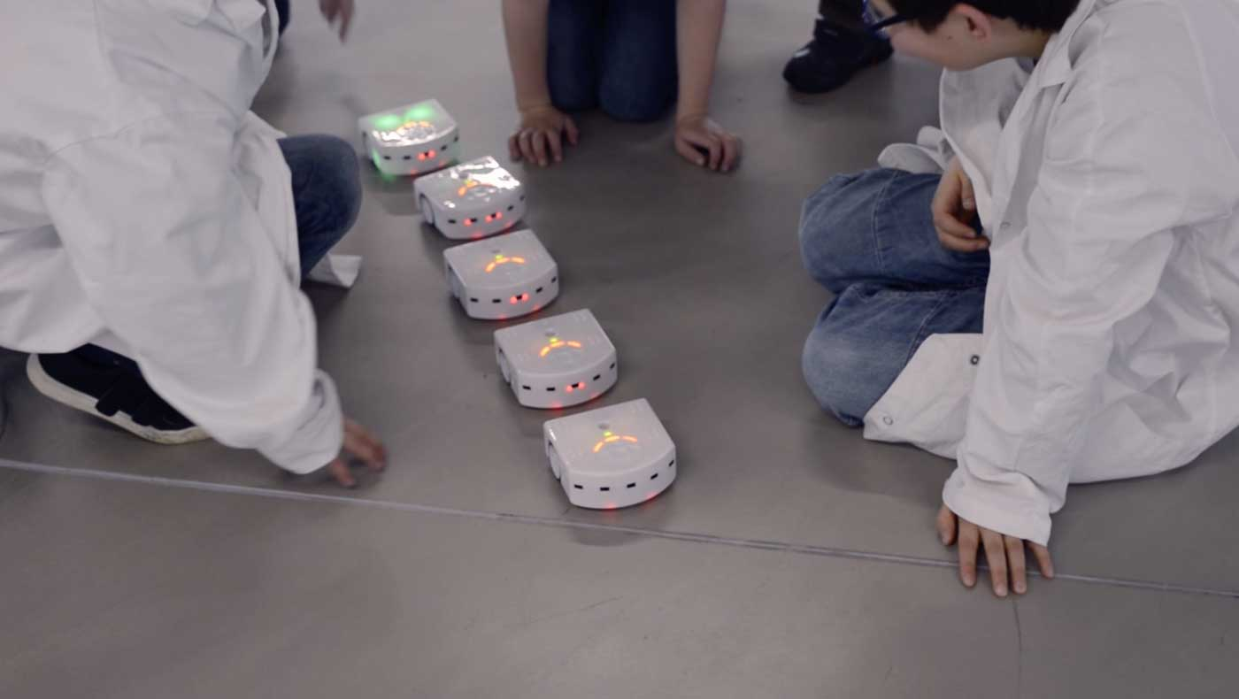 Kids playing with Epfl's Thymios robots following each other during a Addictlab Academy birthday party lab